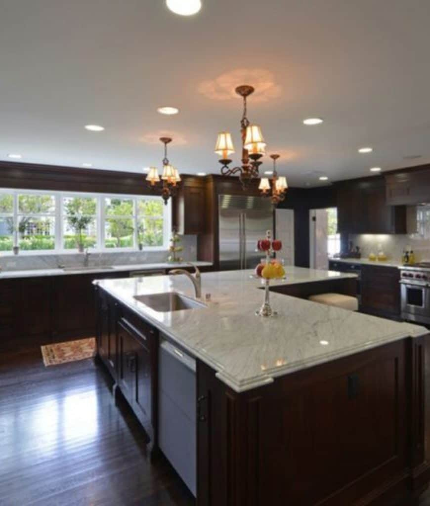 This kitchen showcases shade chandeliers and an L-shaped breakfast island topped with a white marble counter. It has dark hardwood flooring and glazed windows allowing natural light in.