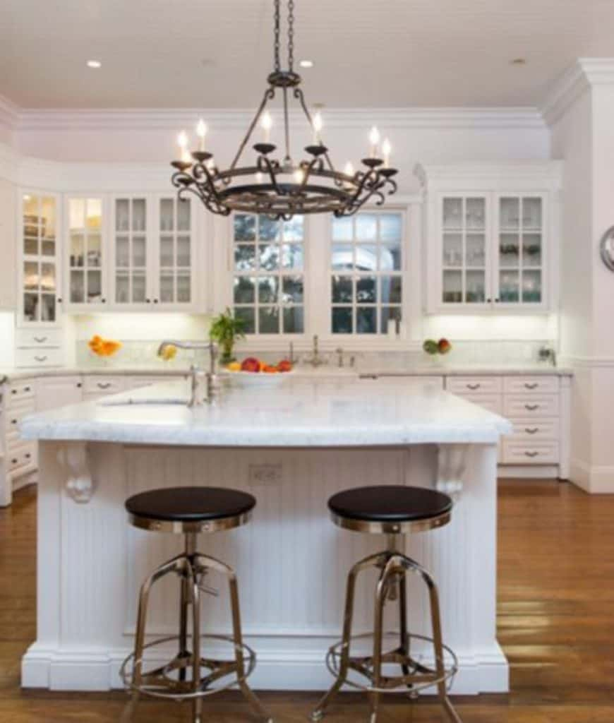 A pair of metal barstools sit at a beadboard central island lighted by a candle chandelier in this kitchen with white cupboard and glass front cabinets.