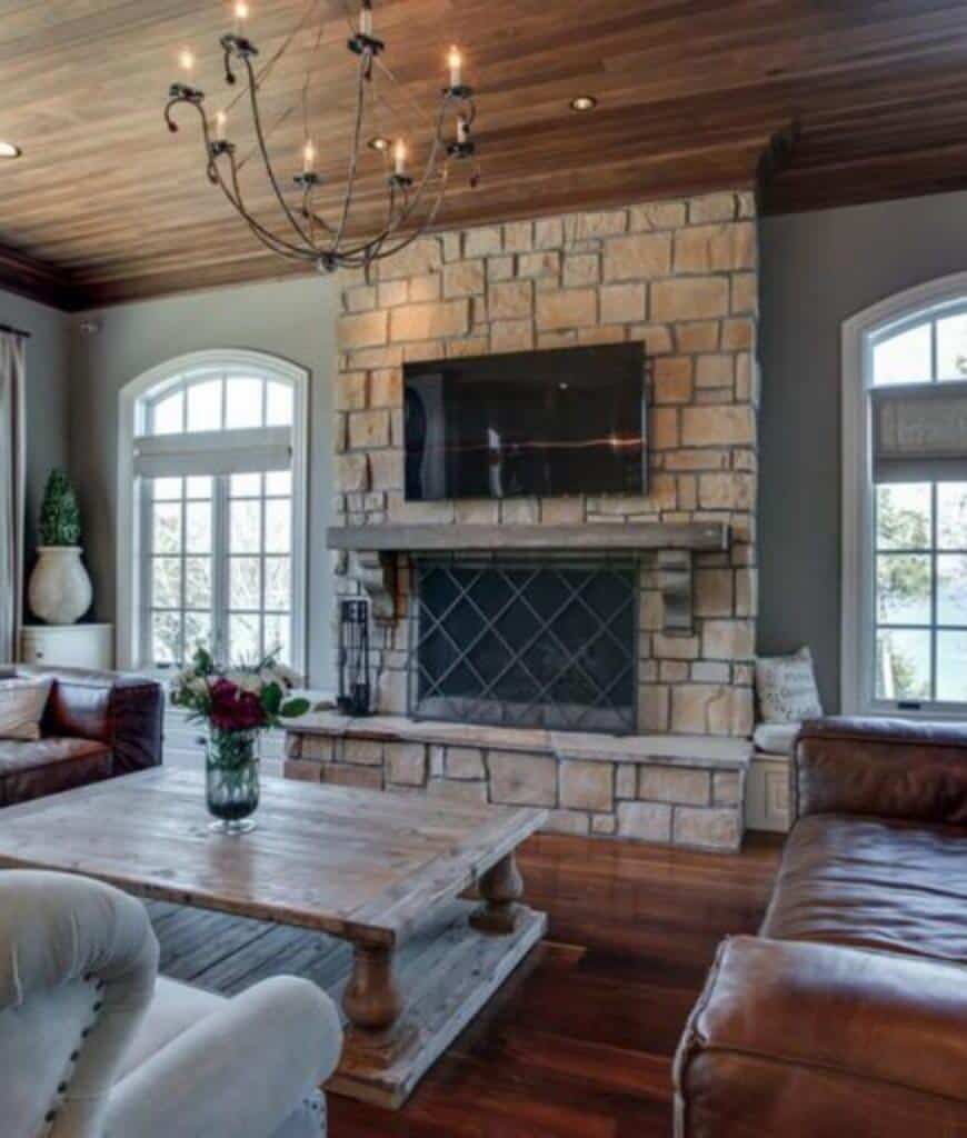 Cozy living room features rich wood plank flooring that complements with the ceiling mounted with recessed lights and chandelier. It has a rustic coffee table and brick fireplace covered with a metal screen.