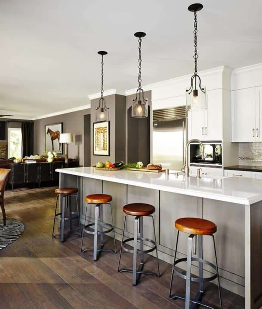 An open kitchen with natural wood plank flooring and wainscoted breakfast bar lined with black metal stools and classy glass pendants.