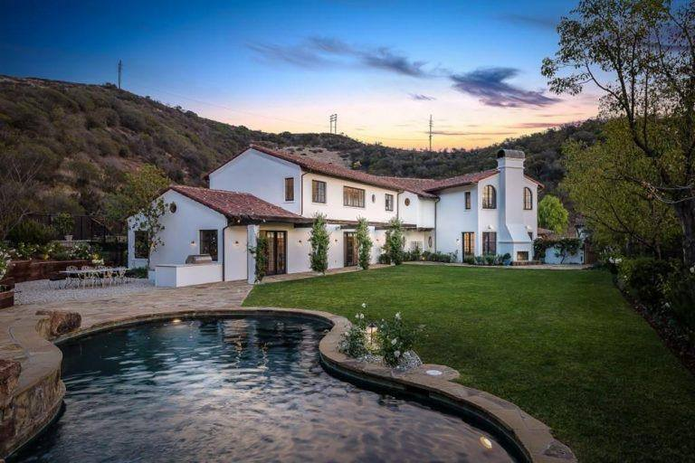 The Spanish home is designed to have an L-shape to accommodate a sprawling well-manicured lawn lined with <a class=