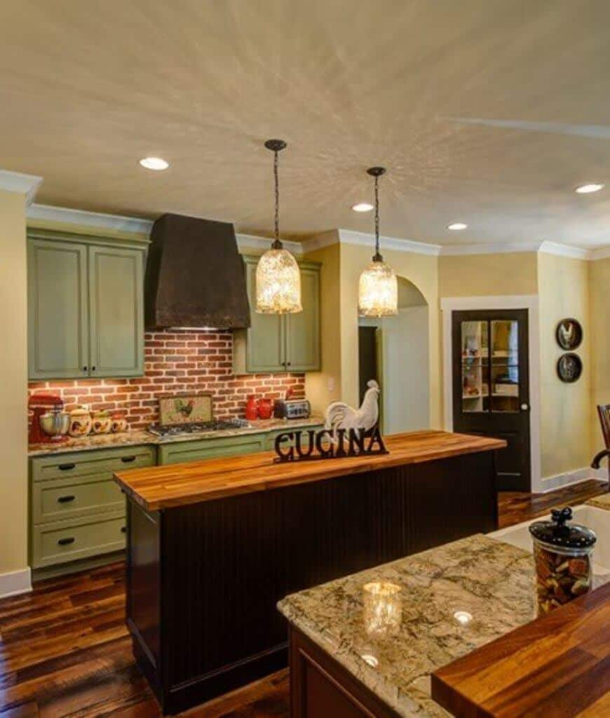 Southwestern kitchen features dark wood island bar lighted by fancy glass pendants and mint green cabinetry accented with a red brick backsplash.