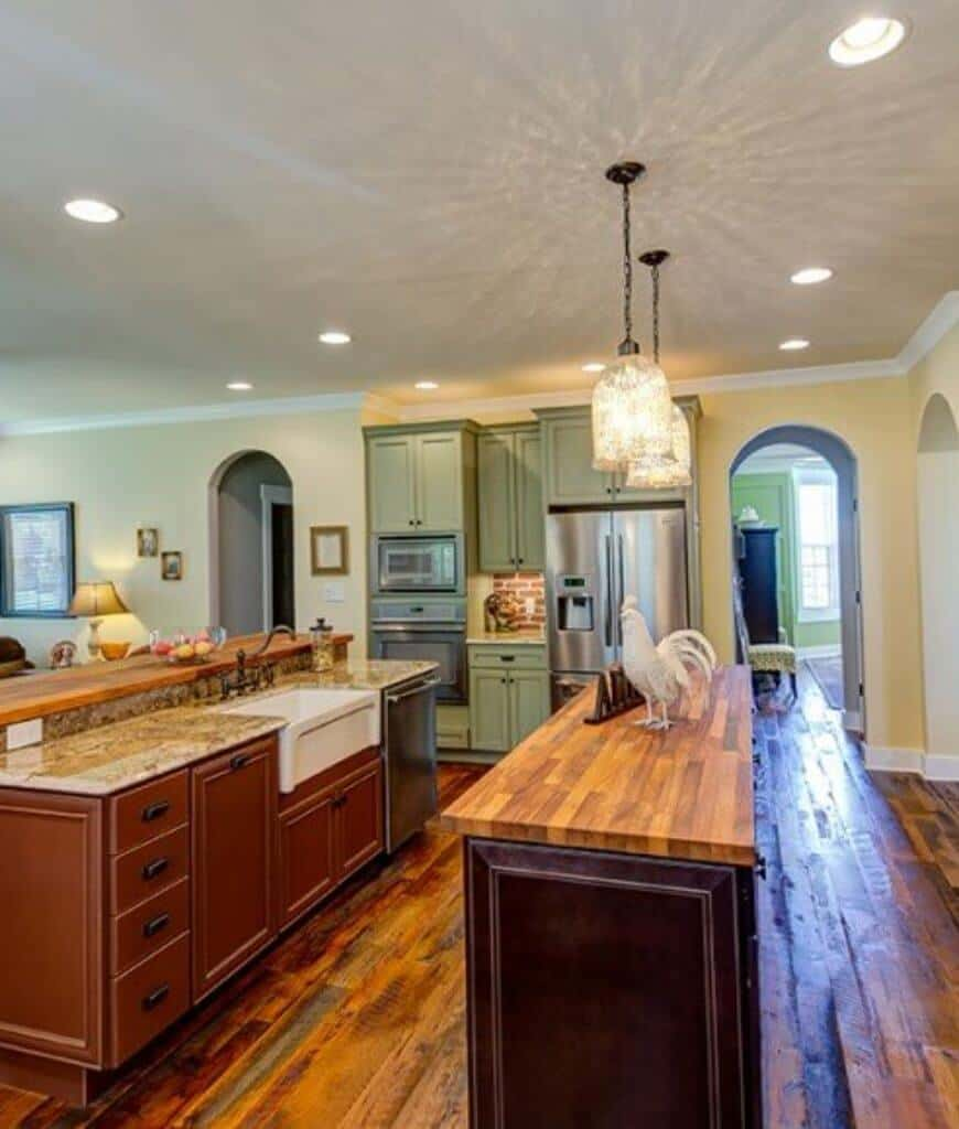 Southwestern kitchen with mint green cabinetry and double kitchen islands illuminated by fancy glass pendants and recessed ceiling lights.