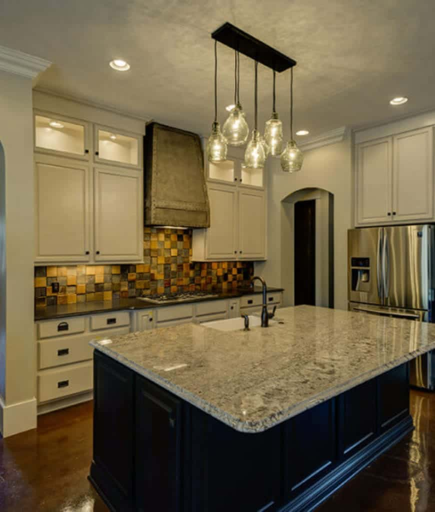 Marvelous kitchen offers glass pendants and a black central island contrasted with white cabinetry that's highlighted by a stylish checkered backsplash.
