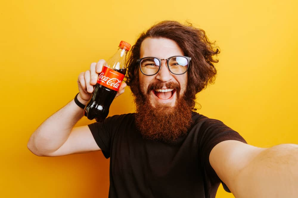 Man holding a bottle of Coca Cola
