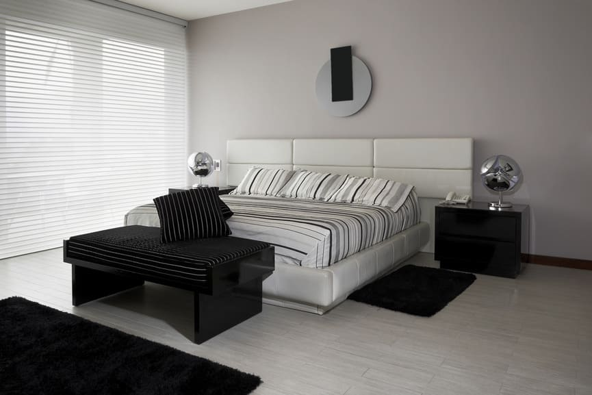 Contemporary master bedroom with black furniture and rugs, along with silver table lamps on both side of the bed.