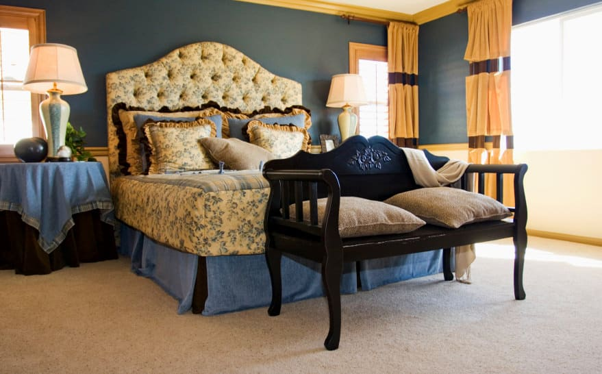 A master bedroom featuring a luxurious-looking bed surrounded by elegant blue walls and carpet floors.