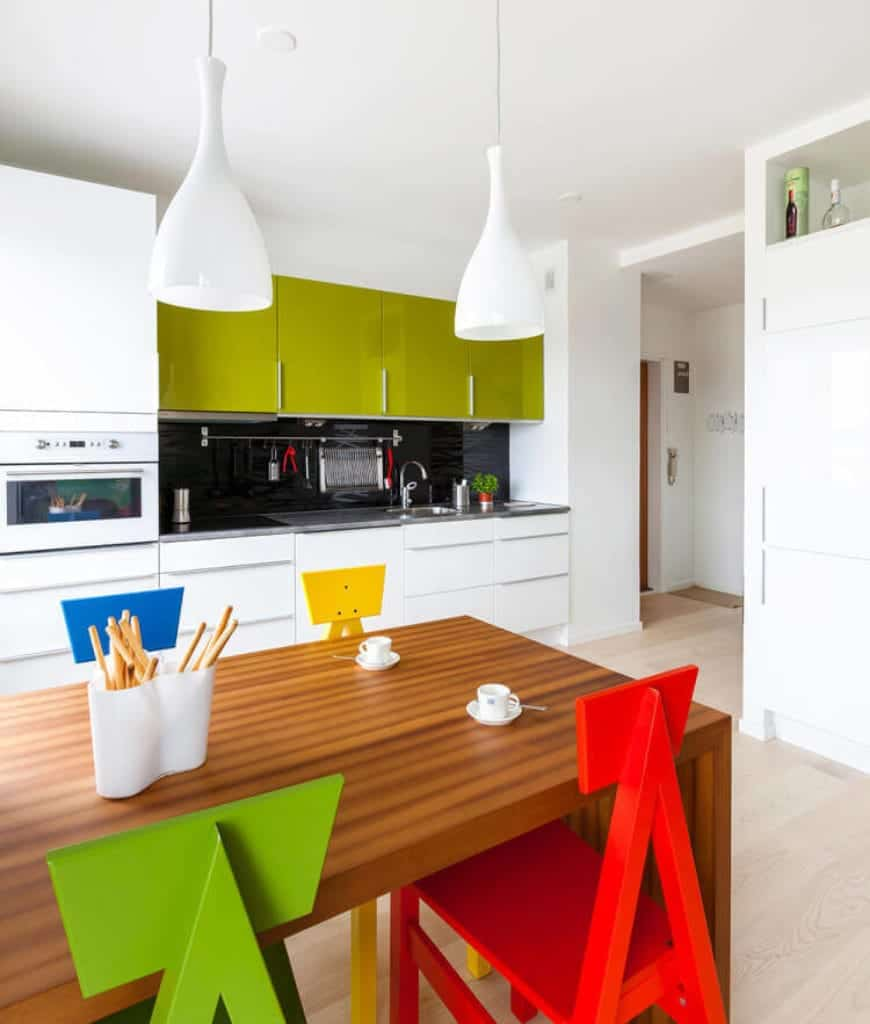 Lively kitchen accented with green upper cabinetry and multicolored chairs surrounding a wooden table that 's lighted by white pendants.