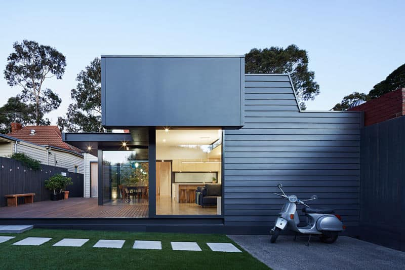 A modern backyard look with concrete steps on a well-manicured lawn. There's a deck area as well.
