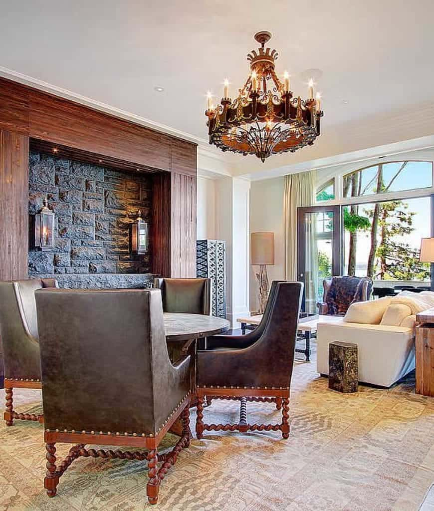 Marvelous living room features two seating areas lighted by wall sconces and a gorgeous chandelier. It includes a brick fireplace and a French door that opens to the balcony.