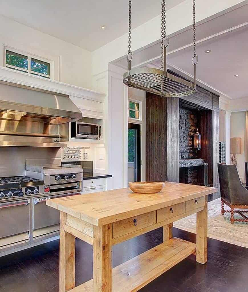 An oval shaped pot rack stands over the natural wood breakfast table topped with a wooden bowl in this kitchen with white cabinet and stainless steel appliances.