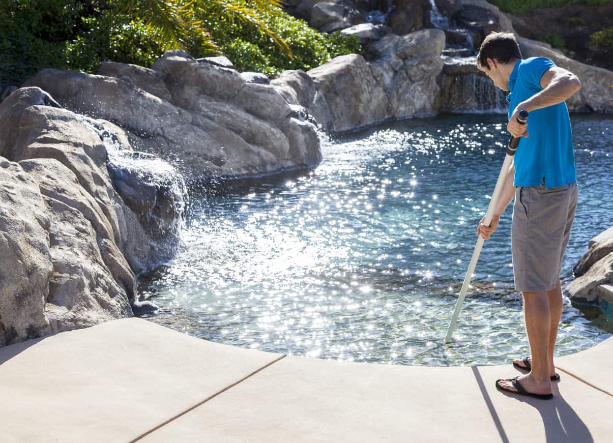 Man cleaning swimming pool with brush