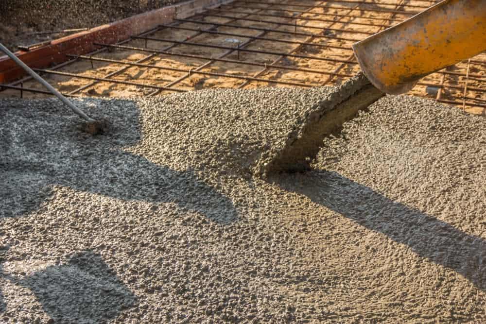 Заливка готового бетона после укладки стальной арматуры для строительства дороги