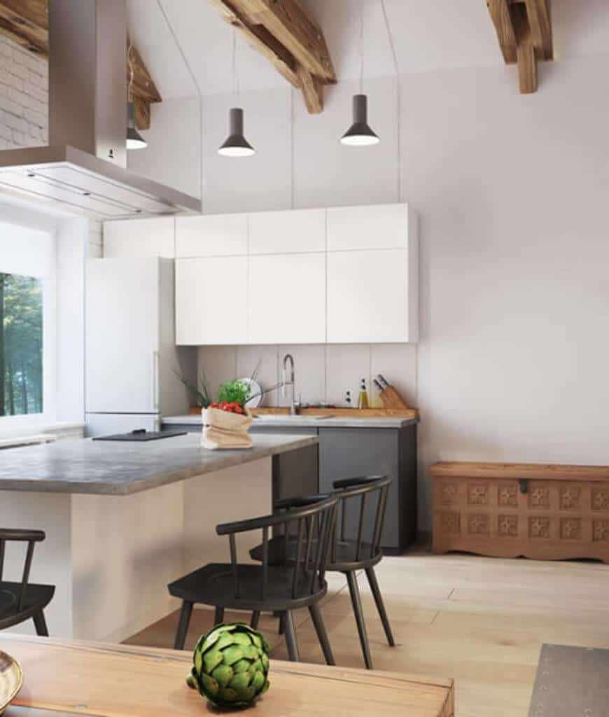 This kitchen showcases a central island accompanied by black round back chairs and an ornate wooden bench that sits next to the white and black cabinetry.
