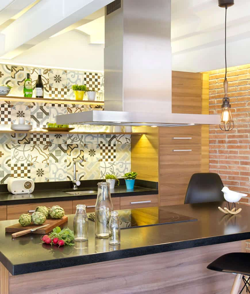 A large stainless steel vent hood stands over the granite top breakfast island in this kitchen with smooth wood cabinetry highlighted by decorative backsplash tiles that are mounted with floating shelves.