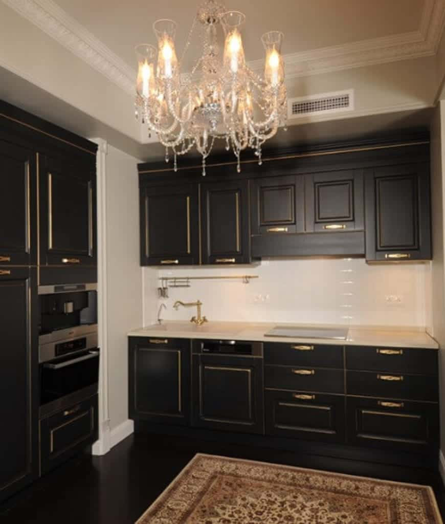 Fabulous kitchen illuminated by a crystal chandelier that hung from the ornate tray ceiling. It has a classic area rug and elegant black cabinetry beutifully contrasted with a white backsplash and countertop.