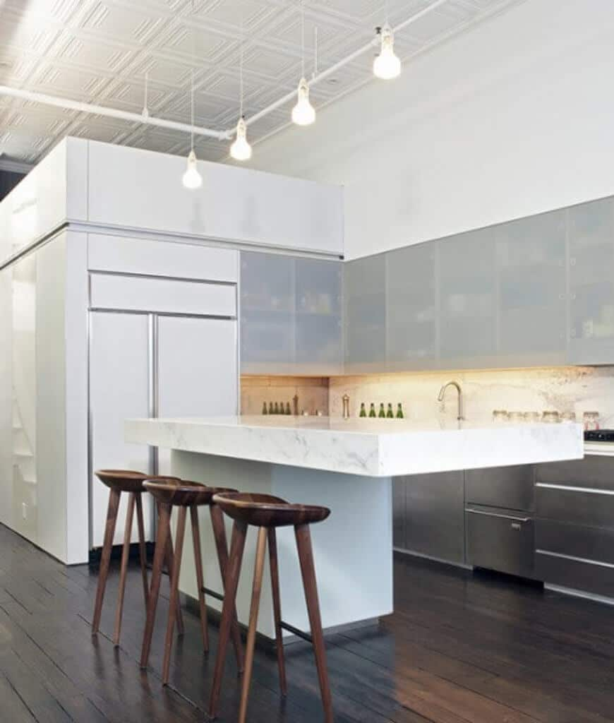 Industrial kitchen with frosted glass front cabinetry and a marble top breakfast bar lined with wooden stools and bulb pendants that hung from the white ornate ceiling framed with exposed pipes.