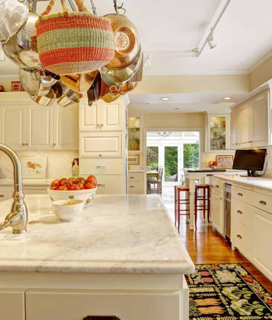 A closeup look at this kitchen with a pot rack suspended over the marble top breakfast island that matches with the white cabinetry. It has beige walls and hardwood flooring topped by a black rug.