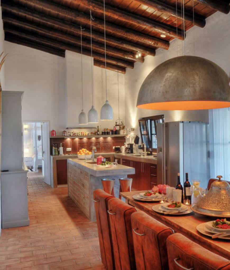 Rustic kitchen features brick flooring and wood beam ceiling with hanging dome pendant lights. It is furnished with a natural wood dining table and brown leather chairs.