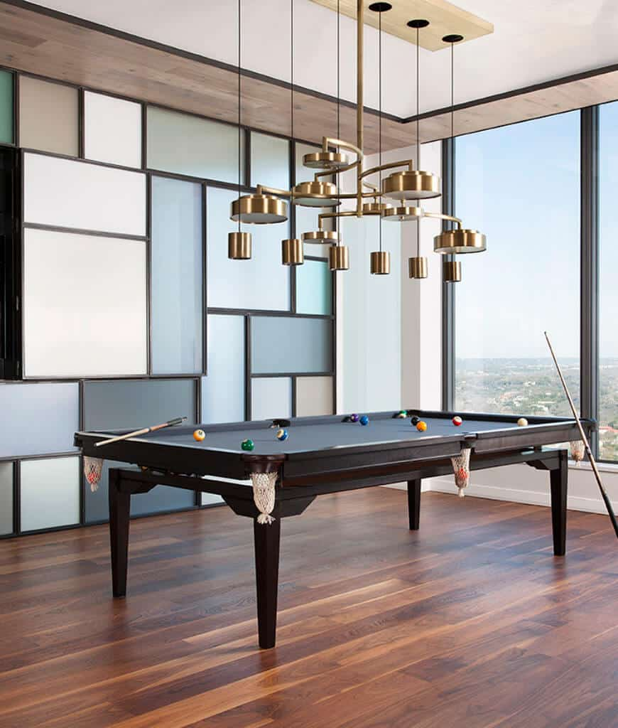 Spacious entertainment room accented with paneled walls and brass pendants that hung over the black pool table. It has wood plank flooring and panoramic windows overlooking a breathtaking view.