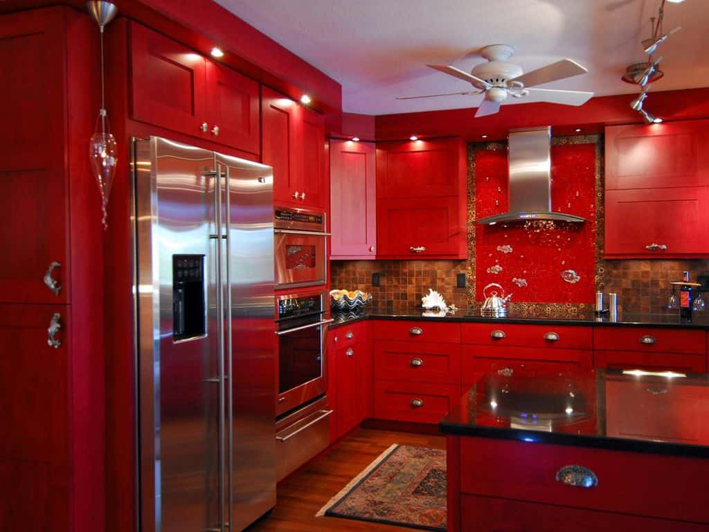A red kitchen featuring red counters, cabinetry and center island with black granite countertops.