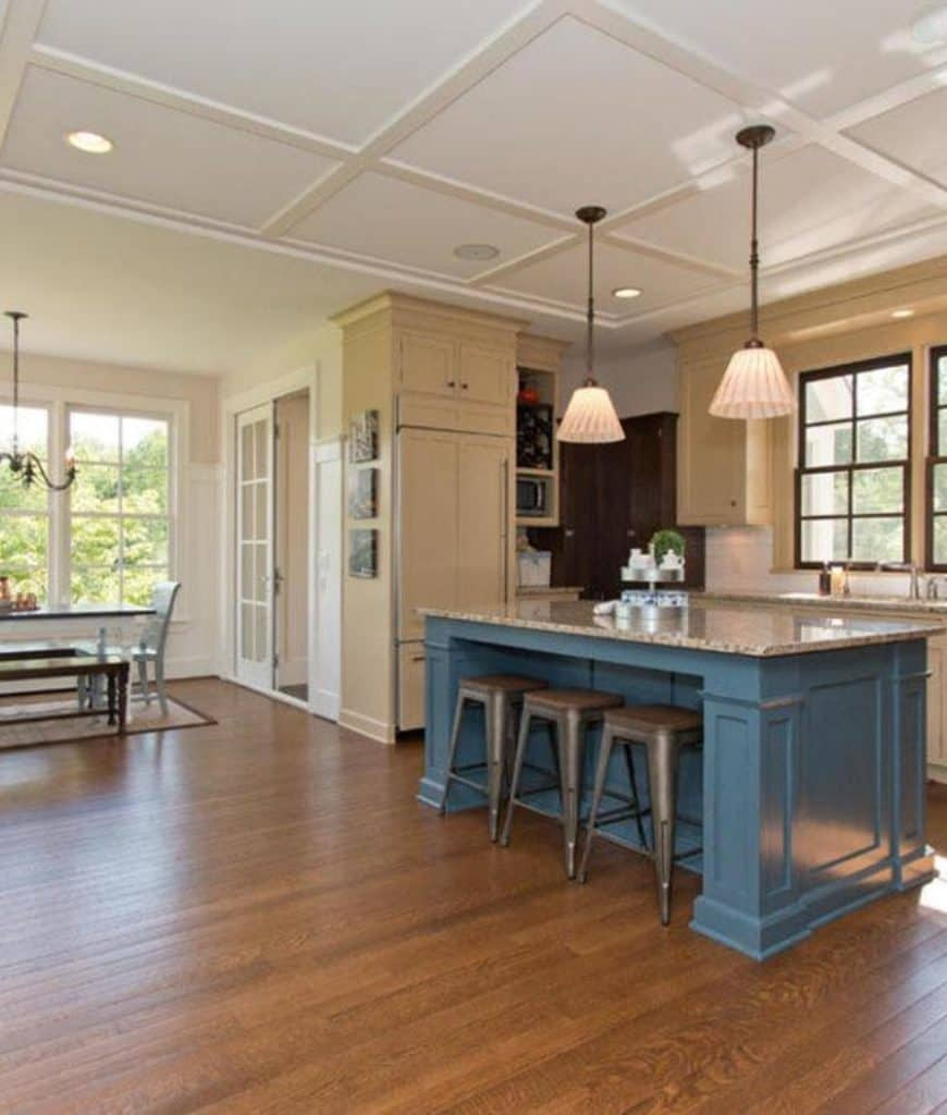 Expansive dine-in kitchen accented by a blue breakfast island that's accompanied by gray bar stools and a pair of pendant lights that hung from the coffered ceiling.