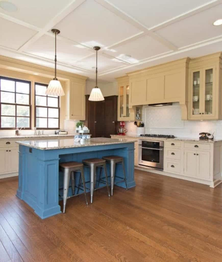 A blue breakfast bar stands out in this kitchen showcasing beige cabinetry and a pair of pendant lights that hung from the coffered ceiling.