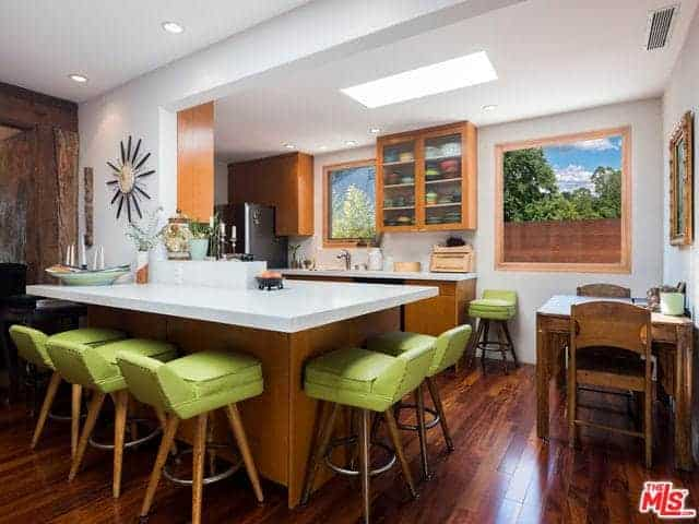 This is a cozy and compact Asian-style kitchen with a hardwood flooring that blends with the wooden kitchen peninsulas that have white countertops. These blend with the white walls that are accented with various Asian artworks.