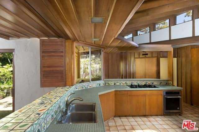 The large kitchen has a J-shaped kitchen peninsula that is adorned with small gray tiles on its countertop augmented by the colorful tiles of the backsplash that has a variety of images on it. This setup is framed with the wooden elements the ceiling, windows, cabinetry and walls.