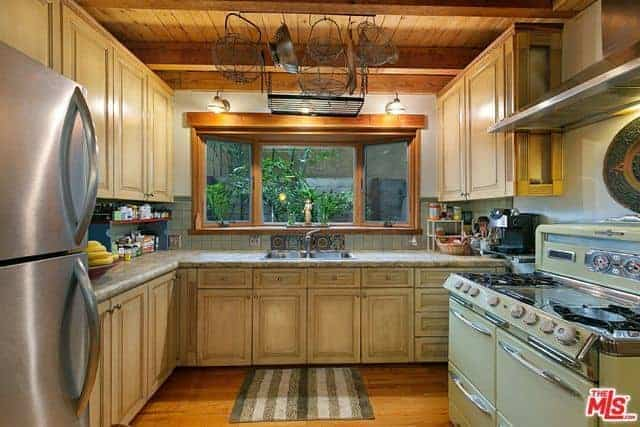 This is a homey and charming Asian-style kitchen with distressed wooden cabinets and drawers on its L-shaped peninsula matching the floating cabinets. This has a nice background of green plants featured by the window above the faucet.