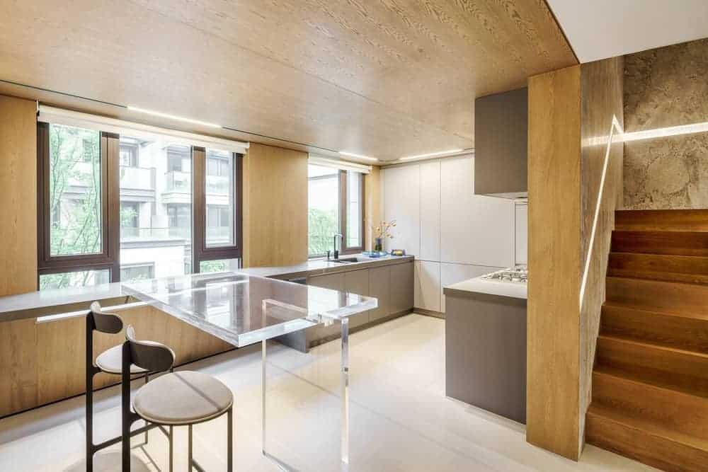 This simple and small kitchen is just beneath the wooden stairs. This matches with the wooden walls and ceiling of this kitchen. This is augmented by the bright white flooring brightened by the natural lights coming in from the windows by the sink area.