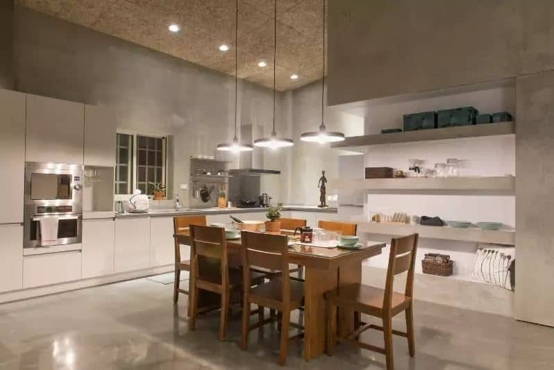 This simple fusion between Asian-style and Industrial-style elements resulted into this lovely design. It has gray concrete walls with built-in concrete shelves. There is also a wooden cork-like ceiling with recessed lights to enhance the lights of the pendant lights that brighten the white L-shaped kitchen.