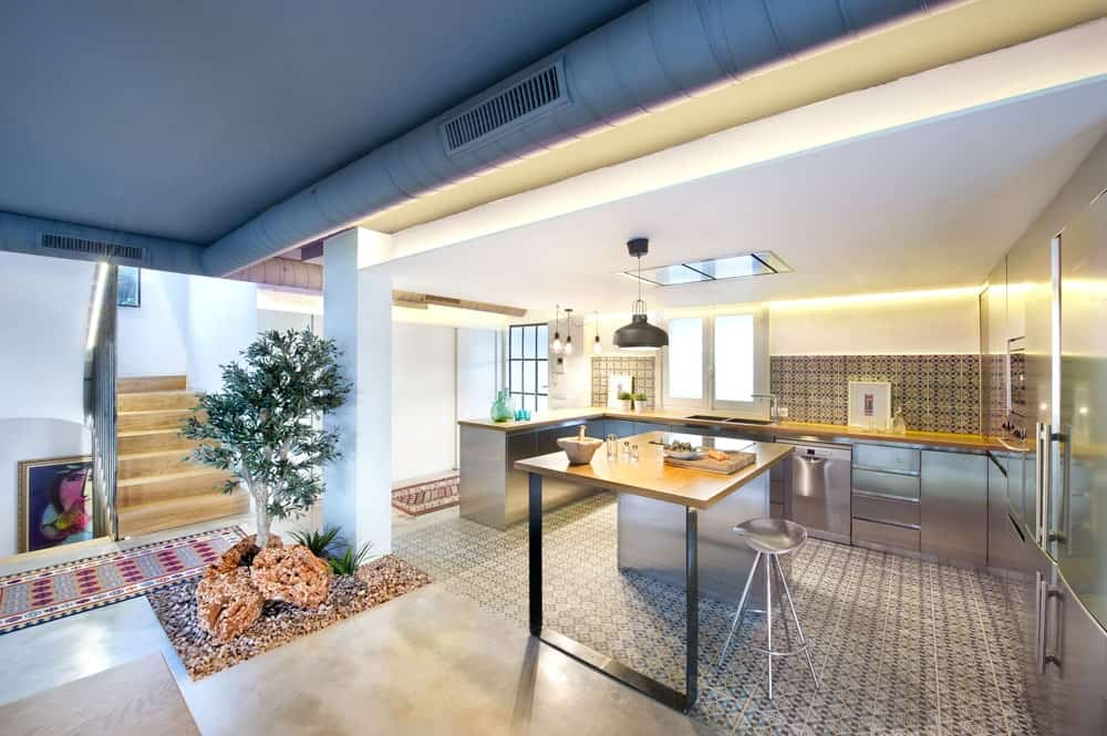 The intricate patterns of the multiple small tiles provide a complex background for the simple stainless steel Kitchen island and peninsula that blend with the modern appliance. These are all augmented by the charming zen garden by the entryway of the kitchen.