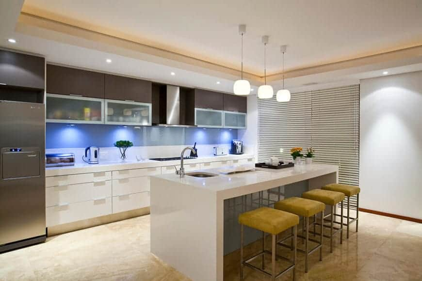 The white marble waterfall countertop of the kitchen island is paired with four cushioned stools with a mustard yellow hue. This is paired with a kitchen peninsula with the same countertop but augmented by the lights that are enhancing the blue backsplash.