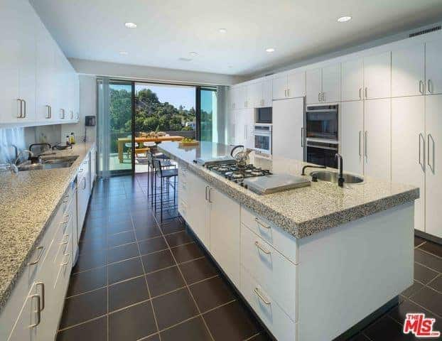 This is a large Asian-style kitchen with enough space for a large kitchen island flanked by a long kitchen peninsula and a large structure on the other side that houses the appliances. All of these have white cabinets and drawers that are contrasted by the black tiles of the floor.