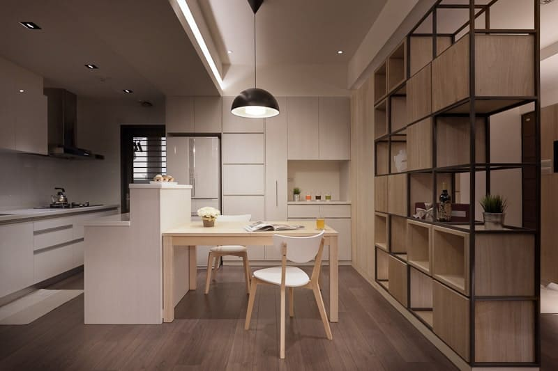 The wooden dining table is pushed against the white wooden kitchen island with white countertops on its two tiers. This tone is mirrored by the kitchen island that stands out against the hardwood flooring. The other peninsula houses the white fridge.