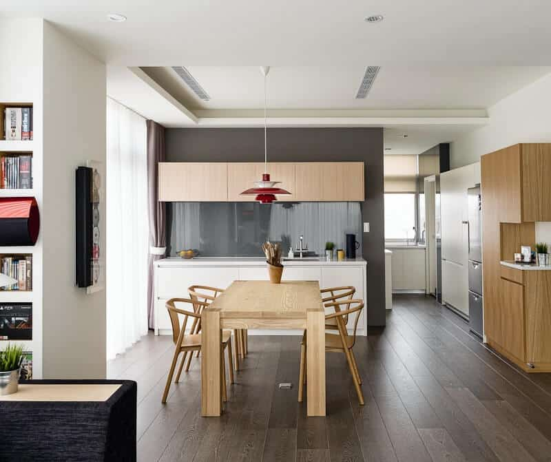 This area is being shared by the dining area's wooden table and chairs as well as the kitchen on the same dark hardwood flooring. This flooring contrasts the white cabinets and drawers of the kitchen peninsula. There is another L-shaped one by the small corner on the right.