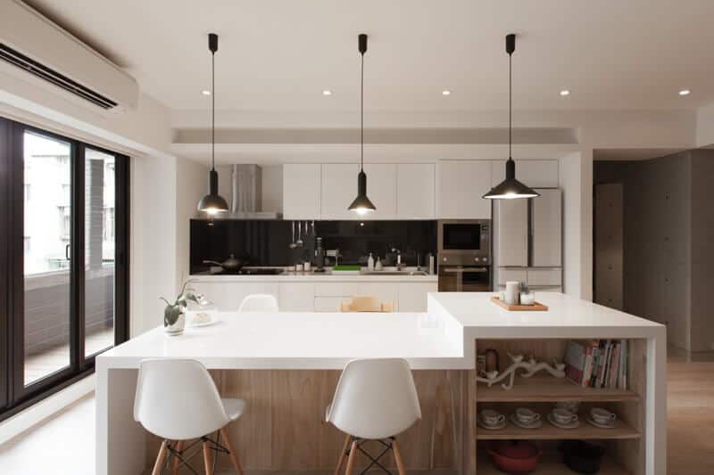 This is a bright Asian-style kitchen due o the abundance of natural lights coming in from the glass sliding doors from the left that lightens up the white waterfall kitchen island counter that has bare wooden shelves and cabinets matching the hardwood flooring.