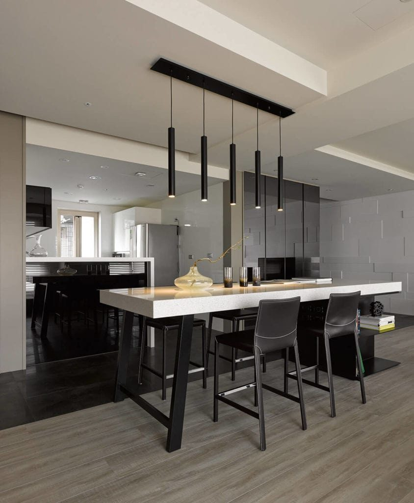 The elegant slim black pendant light hanging over the white countertop of the kitchen island matches with the kitchen peninsula that is contrasted by its white countertop with a waterfall finish and design. These are all complemented by the black tiles of the floor.