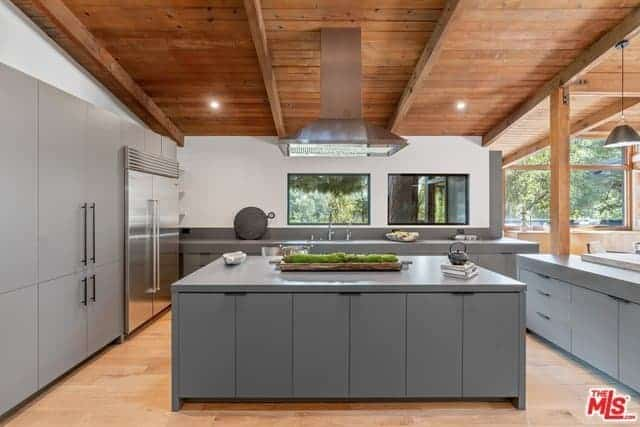 This beautiful modern kitchen has consistent gray cabinets and drawers on all the structures of the kitchen matching the modern appliances. These are all sandwiched by the wooden ceiling with exposed wooden beams as well as the hardwood flooring.