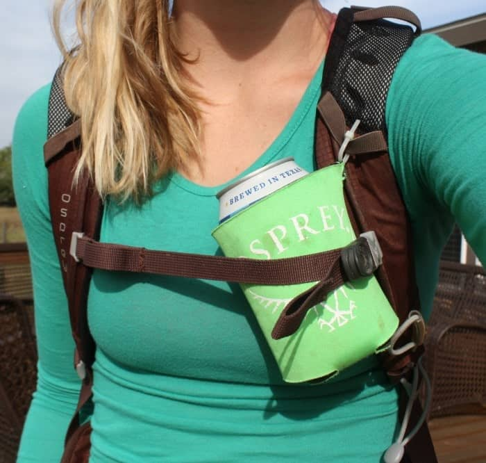 Woman wearing a backpack with a drink carrier attached by a zip tie.