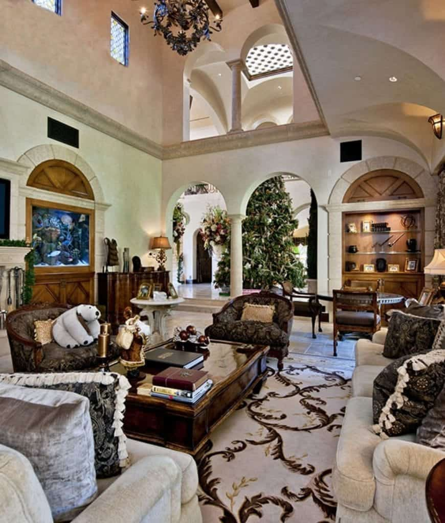 Grand living room with open archways and tiled flooring topped by a classy rug. It is lighted by a wrought iron chandelier that hung from the high beamed ceiling.