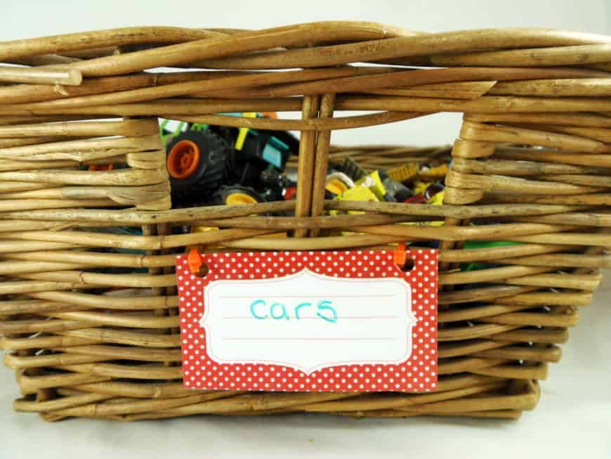Basket of toy cars with a label attached by a zip tie.