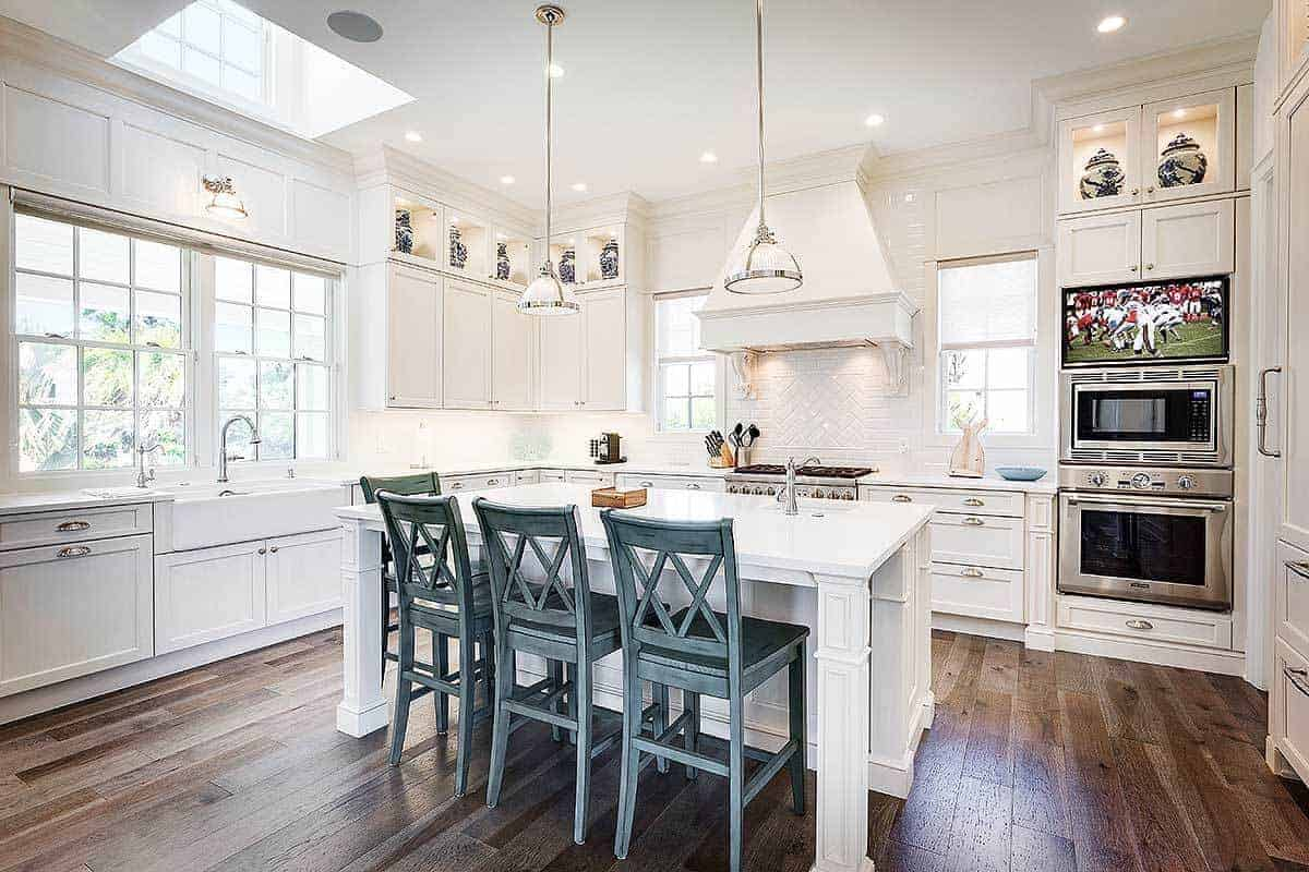 The dark hardwood flooring of this kitchen contrasts the brilliant white shaker cabinets and drawers of the kitchen island that is paired with green stools and the kitchen peninsula that houses the stainless steel appliances.