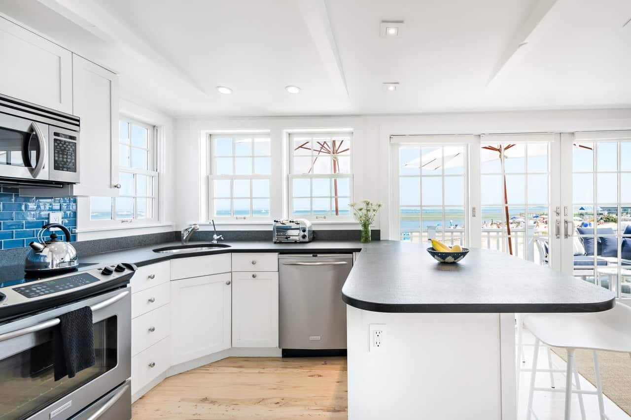 This simple and small Beach-style kitchen has no space for a kitchen island. This is countered with a U-shaped peninsula with cabinets and drawers housing the modern appliances that stand out against the white walls and ceiling complemented by the black countertop.