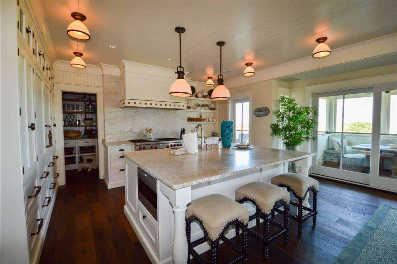 The stand-out elements of this charming white kitchen are the pendant lights and semi-flush lights mounted on the white ceiling that contrasts the dark hardwood flooring. These lights cast off warm lights that elevate the white marble countertops.