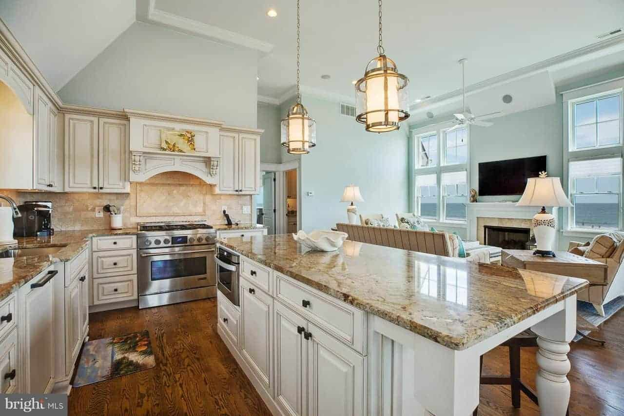 This Beach-style kitchen has elegant brass pendant lights hanging over the large white wooden kitchen island with beige marble countertop that matches those of the L-shaped peninsula. These are given a delightful light blue background of the walls and ceiling.