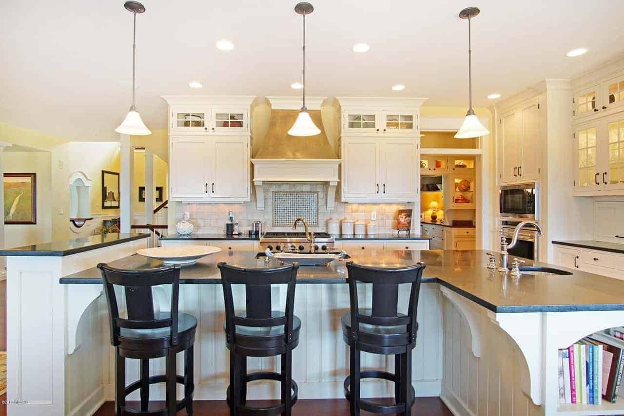The massive white kitchen island has an L-shape followed by its black countertop and a second tier to serve as a divider This kitchen island is big enough for two sinks each paired with beautiful brass faucets illuminated by the yellow pendant light from the white ceiling.