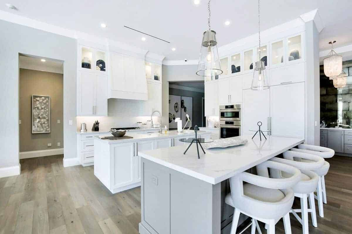 This charming kitchen has a white ceiling that blends with the shaker cabinets and drawers of the peninsula and one of the two kitchen islands that houses the sink area. The other kitchen island has a light gray hue that complements the hardwood flooring.