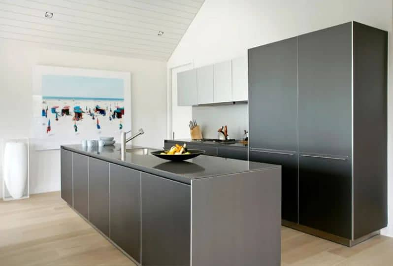 This kitchen has brilliant modern black cabinets and drawers to its kitchen island and peninsula that stands out against the light hardwood flooring as well as with the white walls and white cathedral ceiling.